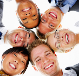 a group of people smiling and looking down in a circle