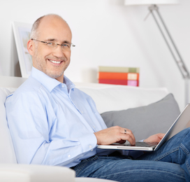 a man smiling and sitting on a couch with his laptop